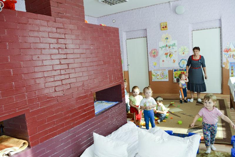 În prezent, sobele imense au doar rolul de decor în sălile pentru copii. În imagine: educatoarea Raisa Chetraru cu micii locuitori ai satului