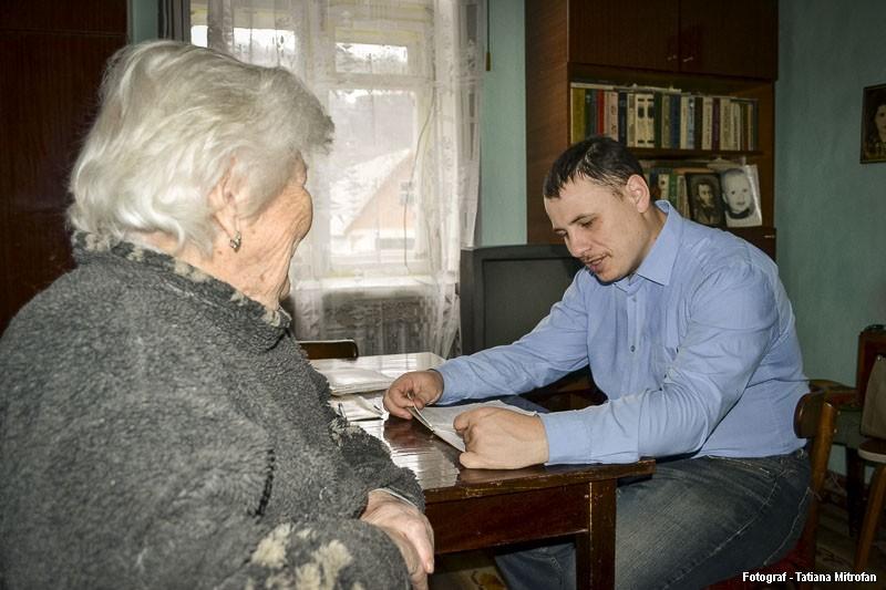 Beneficiara Maria Başchirova şi lucrătorul social Constantin discută despre cheltuielile la facturi din luna precedentă