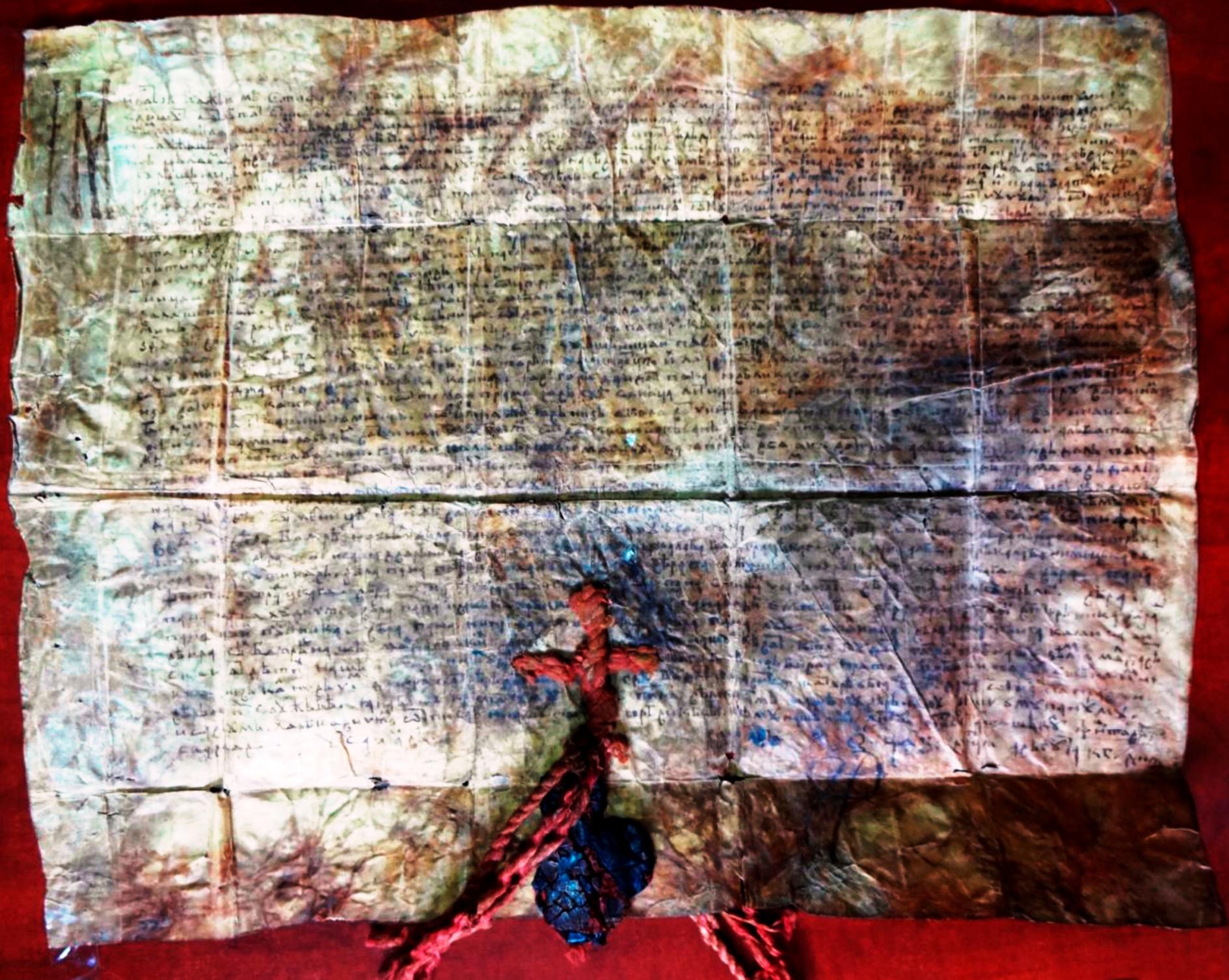 """""""+ Din mila lui Dumnezeu, noi, Ştefan voievod, domn al Ţării Moldovei"""", fragment din hrisovul cu caracter îndoielnic din 23 august 1469. Pergament galben-maro, prost prelucrat, rupt la îndoituri. Cerneală cafenie (probabil, chinovar decolorat). Pecete de smoală neagră cu sigiliu roşu, deteriorată, atârnată pe fir răsucit, cafeniu, de mătase, decolorat. Dimensiuni: 435 × 330. Arhiva personală a academicianului Demir Dragnev (publicat în 2016 de Sergiu Bacalov și Larisa Svetlicinâi de la Institutul de Istorie al AȘM)"""